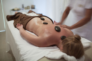 Woman during hot stone therapy at beauty spa