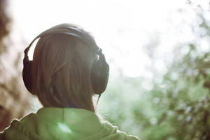Woman in headphones against bright sunlight