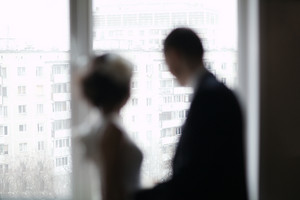 Bridal pair looking out the window