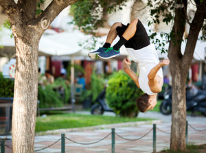 Young sportsman doing front flip in the street