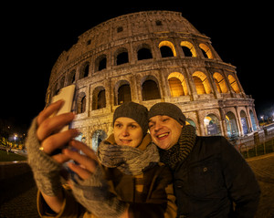 Happy couple making selfie by coliseum at night