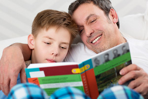 Son and father reading book together