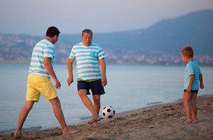 Family team of three playing football at the seaside
