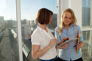 Two businesswomen standing against of city view from window