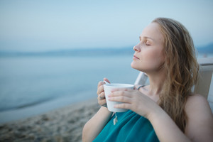 Woman with closed eyes enjoying a cup of tea
