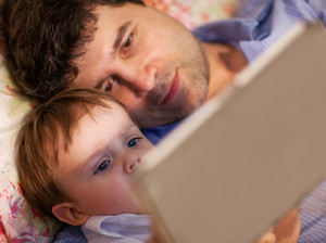 Man and little boy playing with tablet in bed
