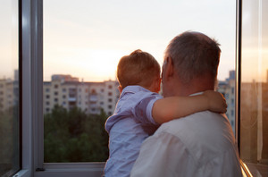 Grandfather and grandson embracing on the balcony