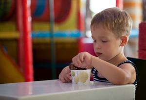 Little child eating chocolate ice cream