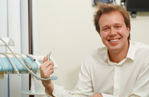 Laughing man with tousled hair holding dental tool