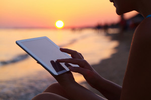 Woman using pad outdoor at sunset