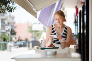 Woman with phone in outdoor cafe