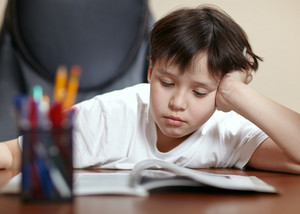 School boy studies hard over his book at home