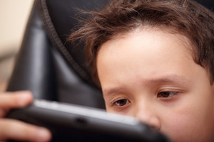 Boy tired of playing his portable game console