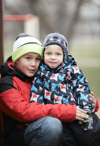 Two adorable young brothers outdoors in winter
