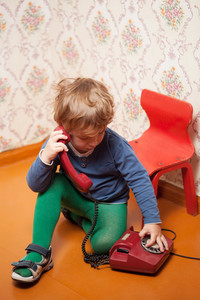 Young boy using red phone