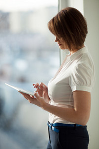 Side view of adult woman using tablet