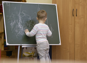 Little boy drawing on a chalkboard at kindergarten