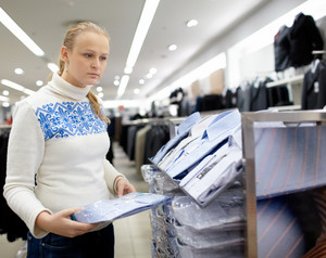 Woman is choosing shirt for man