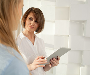 Portrait of brunette woman with tablet looking at her colleague