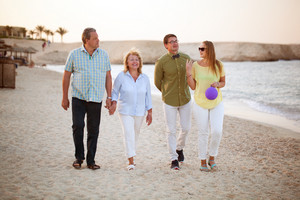 Young and senior couples walking along the coast