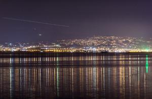 Light streak in sky over city at night