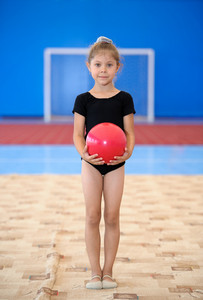 Little gymnast girl with red ball