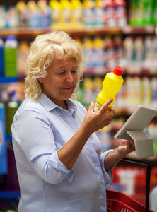 Senior woman with pad reading the detergent label