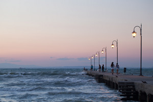 People walking along the pier in evening