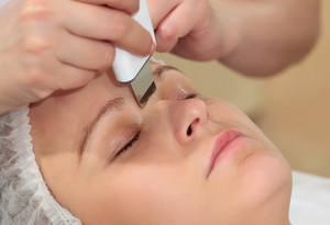 Woman under procedure of ultrasonic facial cleaning