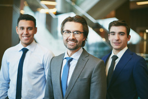 Happy Mature Boss Looking At Camera With Two Employees On Background