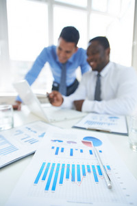 Business Documents At Workplace With Two Businessmen Networking On Background