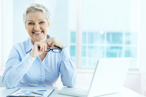 Portrait Of Happy Mature Businesswoman Looking At Camera In Office