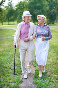 Happy Seniors Talking While Taking A Walk In The Park In Summer