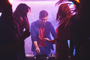 Young Deejay Adjusting Sound With Dancing Girls Near By