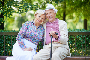 Happy Seniors Sitting On Bench In The Park And Looking At Camera
