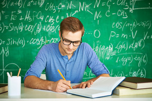 Portrait Of Handsome Student Carrying Out Graduation Test On Background Of Chalkboard