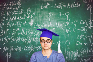 Portrait Of Handsome Student In Graduation Hat And Eyeglasses Looking At Camera On Background Of Chalkboard