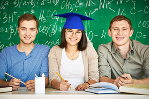 Portrait Of Three Smart Students Looking At Camera With Chalkboard On Background