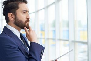 Image Of Young Businessman With Touchpad Looking Through The Window In Office