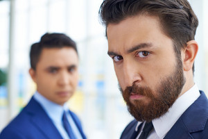 Image Of Bearded Businessman In Formalwear Looking At Camera On Background Of His Colleague