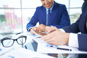 Image Of Businessman Pointing At Document In Touchpad While Interacting With His Partner At Meeting