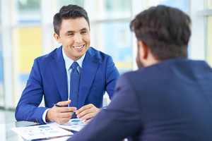 Image Of Handsome Businessman In Suit Communicating With His Colleague At Meeting