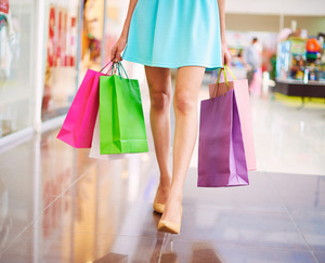 Legs Of Shopaholic With Shopping Bags Walking Down Mall