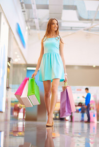 Pretty Young Shopper With Colorful Bags Walking Down Mall