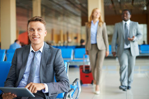 Happy Businessman With Touchpad Looking At Camera With His Partners Walking On Background At The Airport