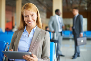 Pretty Businesswoman With Touchpad Looking At Camera With Two Men Interacting On Background At The Airport