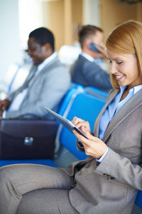 Female Employee Networking In Airport With Two Men Sitting On Background