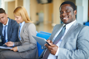 Young African-american Businessman With Digital Tablet Looking At Camera In Airport With Two Co-workers On Background