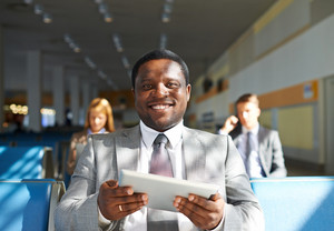 Young African-american Businessman With Touchpad Sitting In Airport With Two Colleagues On Background