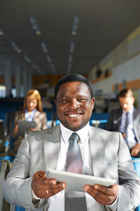 Young African-american Businessman With Touchpad Looking At Camera With Two Colleagues On Background
